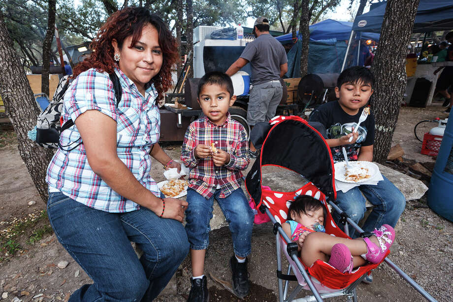 Alejandra Lopez and her children Mauricio (4, from left), Solei (1) and Sabastian (8) take a break to enjoy their funnel cakes at the 47th annual Cornyval on the Helotes Festival Grounds on Saturday, May 4, 2013.  Photo by Marvin Pfeiffer / Prime Time Newspapers Photo: MARVIN PFEIFFER, Marvin Pfeiffer / Prime Time New / Prime Time Newspapers 2013
