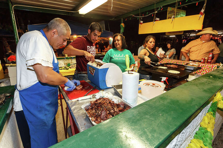 "John Dewitt (from left) slices brisket while Mark Dewitt, Sedma Dewitt and Celest Olvera work to serve customers at the ""John's Beef Fajitas"" booth duringt the 47th annual Cornyval on the Helotes Festival Grounds on Saturday, May 4, 2013. John and his family have been preparing and serving their deliciious brisket tacos for 32 years at Cornyval. Photo by Marvin Pfeiffer / Prime Time Newspapers Photo: MARVIN PFEIFFER, Marvin Pfeiffer / Prime Time New / Prime Time Newspapers 2013"