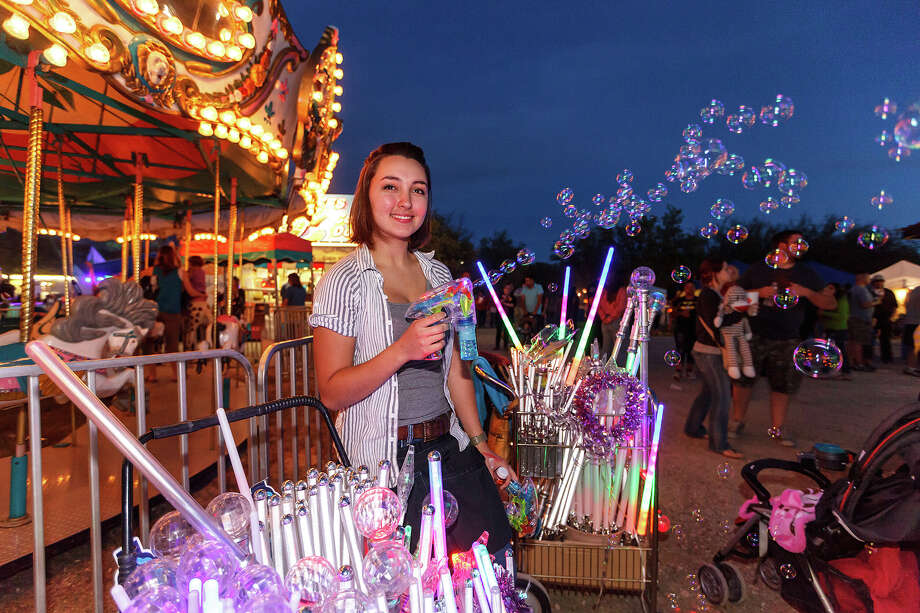 Charli Davenport shoots bubbles out of gun with lights while selling novelites at the Carnival during the 47th annual Cornyval on the Helotes Festival Grounds on Saturday, May 4, 2013.  Photo by Marvin Pfeiffer / Prime Time Newspapers Photo: MARVIN PFEIFFER, Marvin Pfeiffer / Prime Time New / Prime Time Newspapers 2013