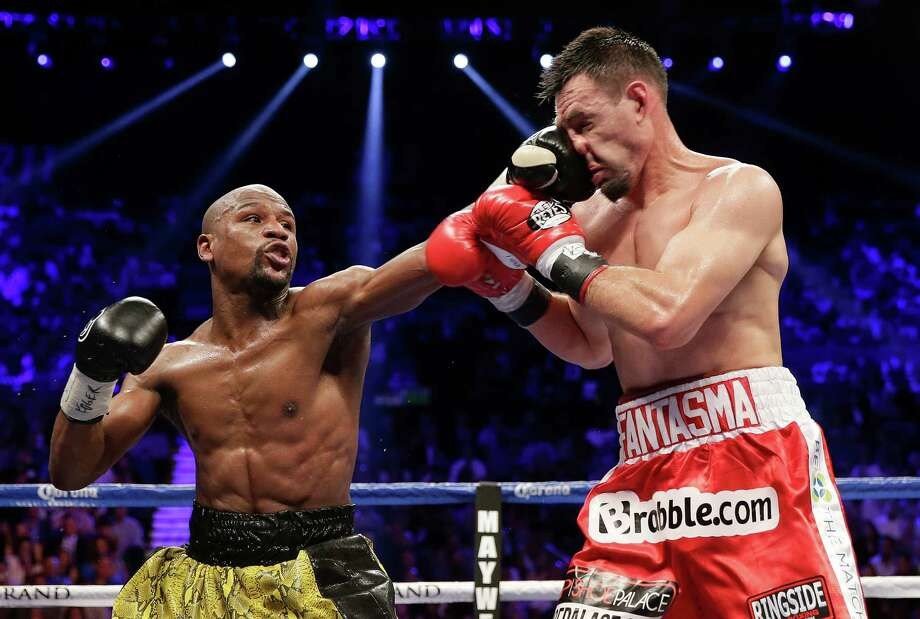 Floyd Mayweather Jr. connects - one of 195 punches he landed - with Robert Guerrero in the fourth round of Saturday's welterweight title fight in Las Vegas. Photo: Isaac Brekken, FRE / FR159466 AP