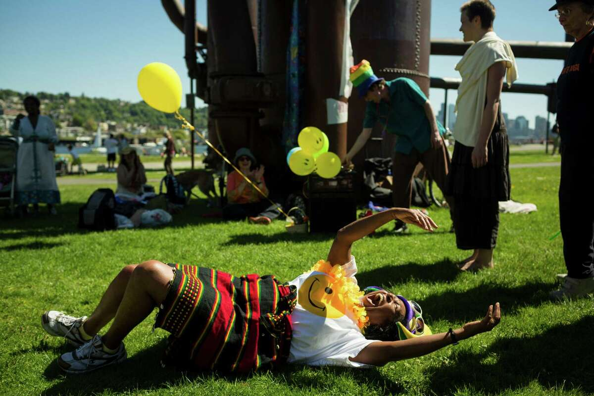 Tita Begashaw collapses while cracking up during a group exercise in celebration of World Laughter Day Sunday, May 5, 2012, at Gas Works Park in Seattle. The group invests in the popular idea that laughter as a body exercise warrants physiological and psychological benefits.