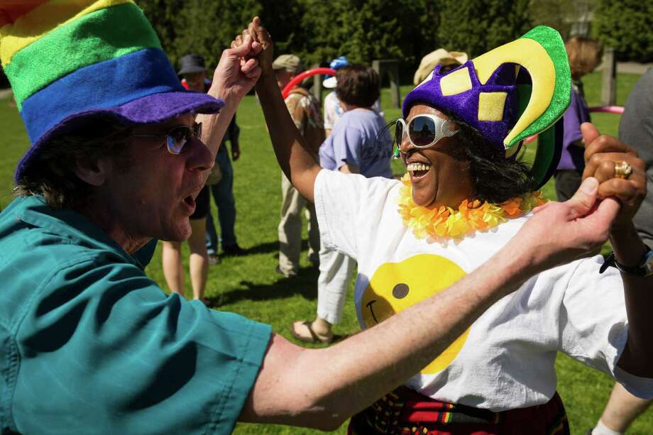 Kevin Wilhelmsen, left, and Tita Begashaw, right, dance while cracking up during a group exercise in celebration of World Laughter Day Sunday, May 5, 2012, at Gas Works Park in Seattle. The group invests in the popular idea that laughter as a body exercise warrants physiological and psychological benefits. Photo: JORDAN STEAD, SEATTLEPI.COM / SEATTLEPI.COM