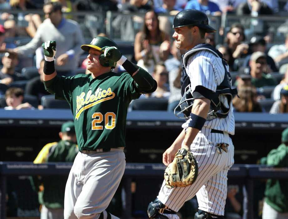 Oakland Athletics Josh Donaldson, left, celebrates as he crosses the plate near New York Yankees catcher Chris Stewart after hitting  a solo home run in the eighth inning of an MLB American League baseball game in New York on Sunday, May 5, 2013. Oakland won the game 5-4. (AP Photo/Peter Morgan) Photo: Peter Morgan