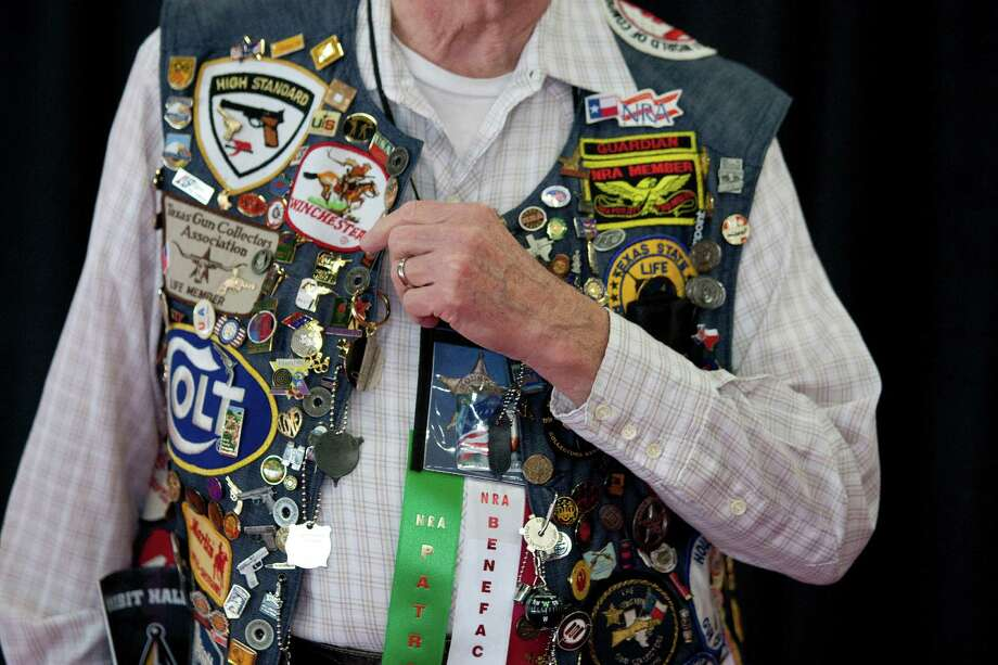 A life-time NRA member, Lee Smith, 79, of Houston shows off his NRA and gun badge collection on his vest at the National Rifle Association's 142 Annual Meetings and Exhibits in the George R. Brown Convention Center Sunday, May 5, 2013, in Houston. 