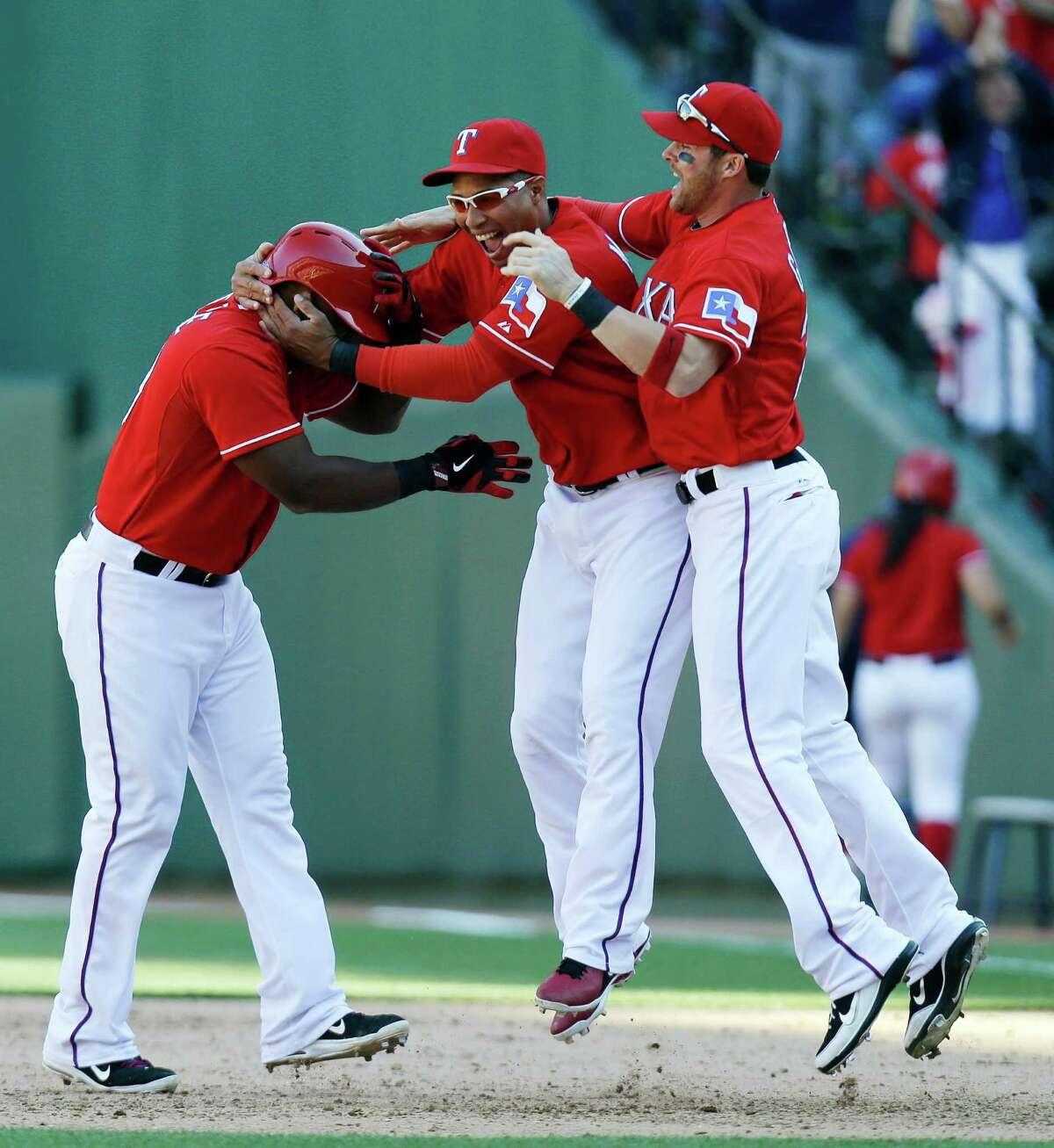 Texas Rangers' Adrian Beltre, left, is grabbed by Leonys Martin, center, and Craig Gentry after Beltre hit the winning RBI single to score Elvis Andrus in the ninth inning of a baseball game against the Boston Red Sox, Sunday, May 5, 2013, in Arlington, Texas. The Rangers won 4-3. (AP Photo/LM Otero)