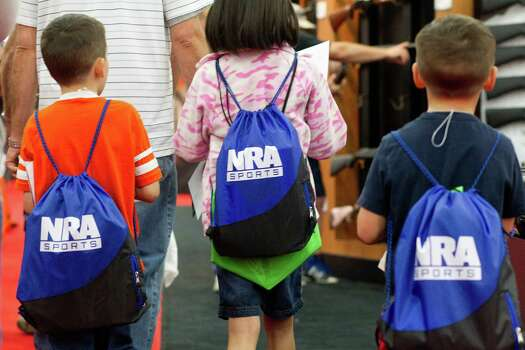 From right, Fisher Bryant, 6, his sister, Bryn, 8, and brother, Tate, 5, walk through the exhibit hall during NRA Youth Day events at the National Rifle Association's 142 Annual Meetings and Exhibits in the George R. Brown Convention Center Sunday, May 5, 2013, in Houston. 
