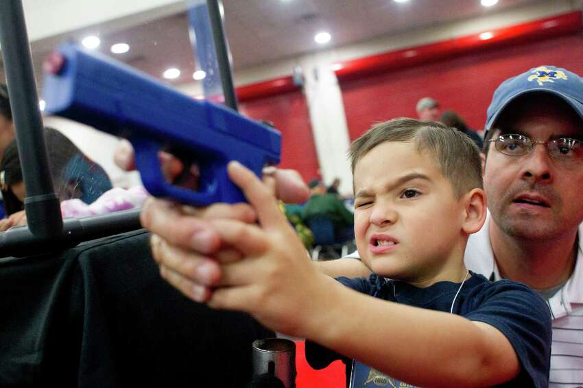 Heath Bryant of Cypress assists his son, Tate, 5, to shoot a target using a video game-style of gun at an exhibit booth during NRA Youth Day events at the National Rifle Association's 142 Annual Meetings and Exhibits in the George R. Brown Convention Center Sunday, May 5, 2013, in Houston. More than 70,000 are expected to attend the event with more than 500 exhibitors represented.