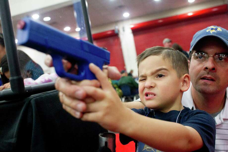 Heath Bryant of Cypress assists his son, Tate, 5, to shoot a target using a video game-style of gun at an exhibit booth  during NRA Youth Day events at the National Rifle Association's 142 Annual Meetings and Exhibits in the George R. Brown Convention Center Sunday, May 5, 2013, in Houston.  More than 70,000 are expected to attend the event with more than 500 exhibitors represented. Photo: Johnny Hanson, Houston Chronicle / © 2013  Houston Chronicle