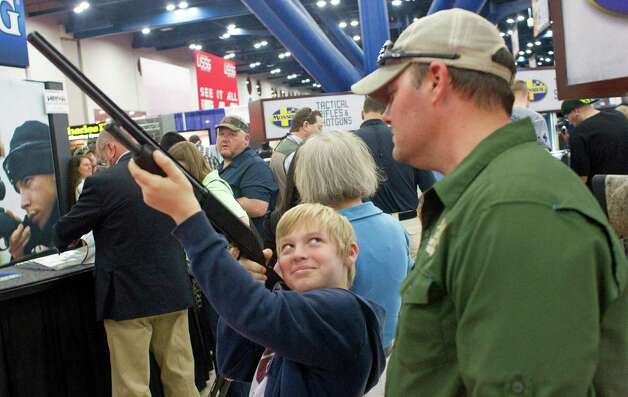 Mason Short, 10, glances up at his father, Le (CQ), from Kountze, as he got a closer look at a shotgun at the Mossberg booth during NRA Youth Day events at the National Rifle Association's 142 Annual Meetings and Exhibits in the George R. Brown Convention Center Sunday, May 5, 2013, in Houston. 