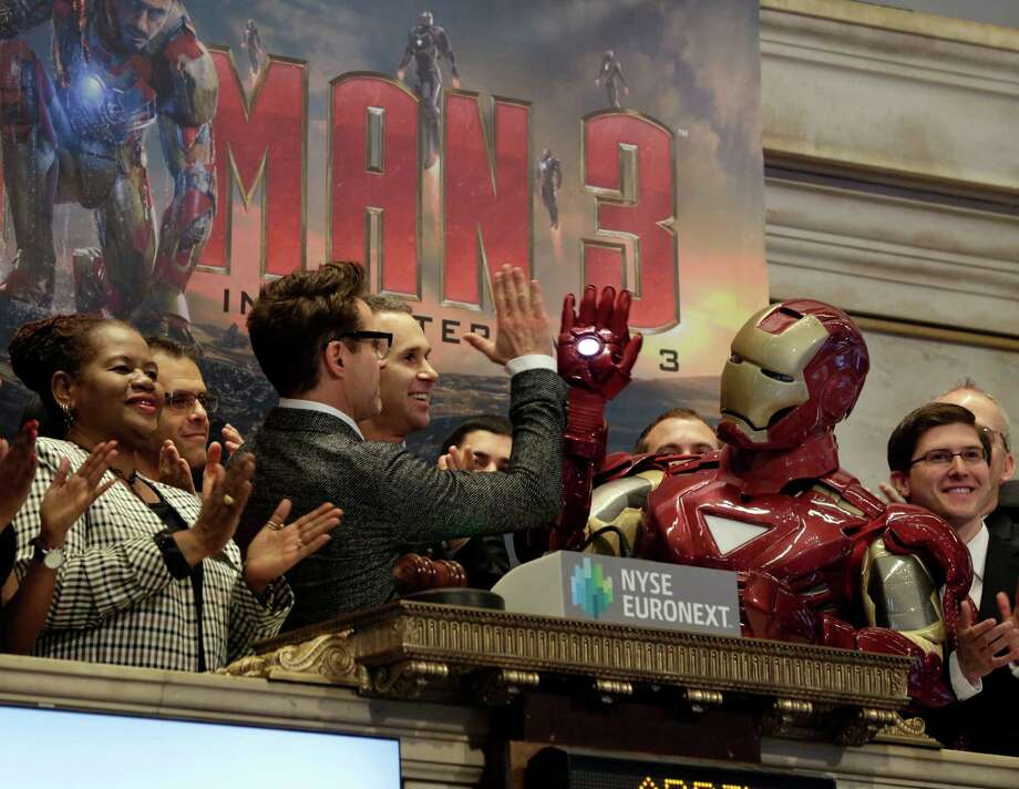 "Actor Robert Downey Jr. gives a high-five to his ""Iron Man"" character during opening bell ceremonies of the New York Stock Exchange, Tuesday, April 30, 2013. Stock prices are opening mostly lower on Wall Street as weak earnings from Pfizer and other companies drag down major market averages.  Downey's film, ""Iron Man 3,"" also starring Don Cheadle and Gwyneth Paltrow, opens nationwide on May 3. (AP Photo/Richard Drew) Photo: Richard Drew"