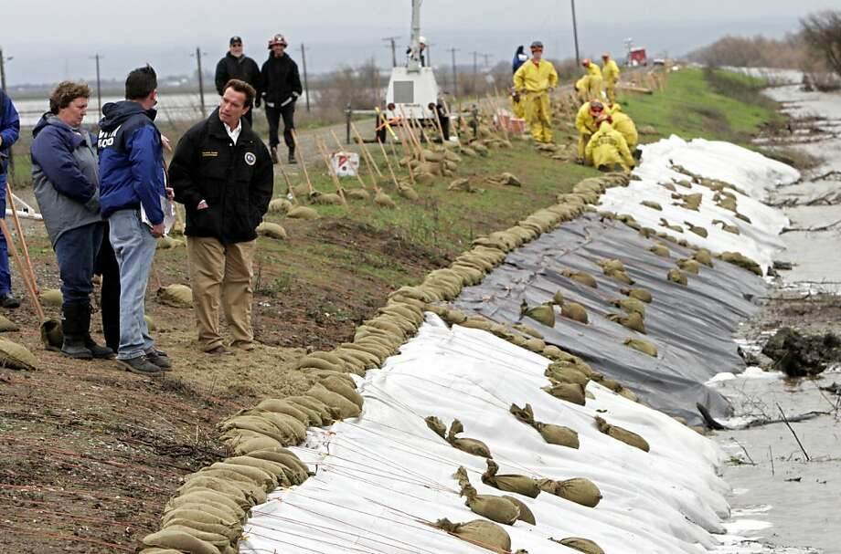 Then-Gov. Arnold Schwarzenegger (in black) tours the Natomas Cross Canal levee near Sacramento in 2006 with Diane Fales (left) and Leslie Harder of the Department of Water Resources. Photo: Rich Pedroncelli, AP