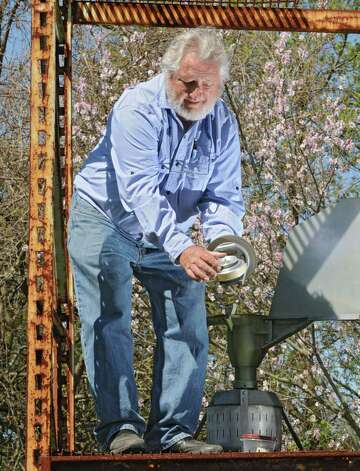 Larry Syzdek, an aerobiologist who counts pollen for a national database, uses a scientific vacuum called a Burkard at his pollen station at his farm on Friday, May 3, 2013 in Clifton Park, N.Y. The air sampler which was made in England collects dry particles such as dust, pollen and fibers from the air and are trapped onto a sticky surface for collection. (Lori Van Buren / Times Union) Photo: Lori Van Buren / 10022271A