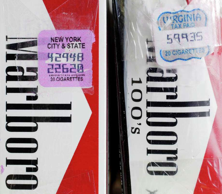 In this Tuesday, April 30, 2013 photo, two packs of Marlboro cigarettes, the one on the left with a New York City and state tax stamp, and on the right a Virginia tax stamp, are displayed for a photo, in New York. New York City's war on smoking is being undercut by light penalties for merchants caught selling cheap cigarettes smuggled in from low-tax states. (AP Photo/Mark Lennihan) Photo: Mark Lennihan