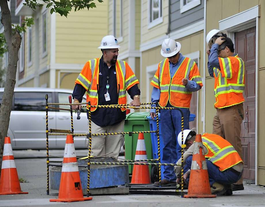 PG&E workers inspect the scene where one of their co-workers was injured due to an electric arc accident in the Bayview area of San Francisco on Sunday, May 05, 2013. Photo: Josh Edelson, Special To The Chronicle
