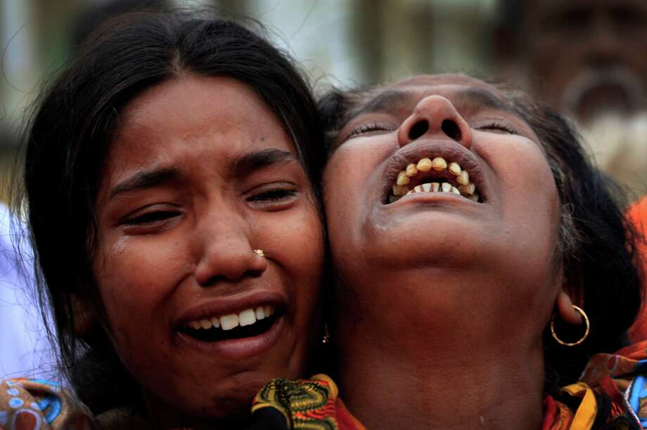 A woman is comforted as she grieves after identifying the body of her daughter, a victim of the garment factory collapse, Sunday, May 5, 2013 in Savar, near Dhaka, Bangladesh. The death toll from the collapse of a shoddily built garment-factory building in Bangladesh continued its horrifying climb, reaching 580 on Sunday with little sign of what the final number will be. The disaster is likely the worst garment-factory accident ever, and there have been few industrial accidents of any kind with a higher death toll. (AP Photo/Wong Maye-E) Photo: Wong Maye-E