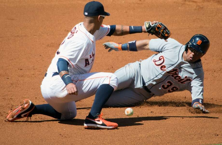 Tigers second baseman Ramon Santiago (39) is safe at second base with a double as the ball gets away from Astros shortstop Ronny Cedeno (13) during the second inning.