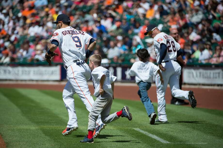 "Participants in the ""Kids Take The Field"" promotion run onto the field with Houston Astros second baseman Marwin Gonzalez (9) and right fielder Rick Ankiel (28) before the game."