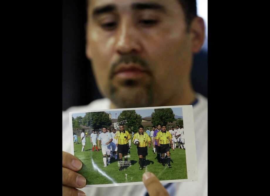 FILE - In this Thursday, May 2, 2013 file photo, Jose Lopez points to an undated photo of Riccardo Portillo, center, his brother-in-law, following a news conference , at Intermountain Medical Center, in Murray, Utah. Portillo, a 46-year-old soccer referee who was punched by a teenage player during a game and later slipped into a coma died Saturday night, May 4, 2013, police said. (AP Photo/Rick Bowmer, File) Photo: Rick Bowmer