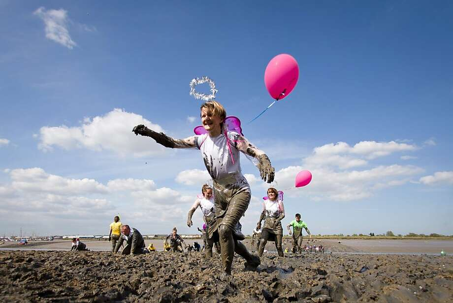 TOPSHOTS Participants reach the finish line of the annual Maldon Mud Race in Maldon, Essex, on May 5, 2013, that sees people running on a short course across a muddy estuary in fancy dress to raise money for charities. AFP PHOTO/Leon NealLEON NEAL/AFP/Getty Images Photo: Leon Neal, AFP/Getty Images