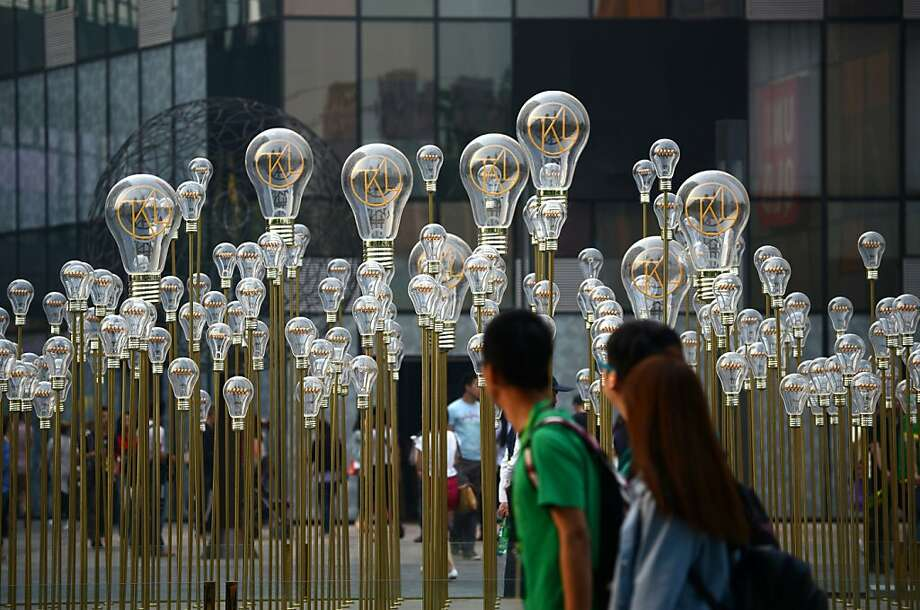 TOPSHOTS People walk past a group of bulbs on display in front of a shopping mall in Beijing on May 5, 2013. Manufacturing activity in China slowed slightly in April from the previous month, official data showed on May 1, in a sign of further weakness in the world's second-biggest economy.         AFP PHOTO/WANG ZHAOWANG ZHAO/AFP/Getty Images Photo: Wang Zhao, AFP/Getty Images