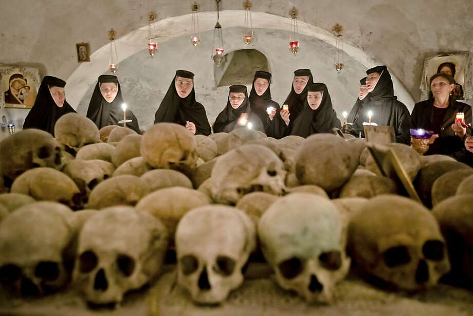Romanian orthodox nuns sing in the ossuary at the Pasarea monastery, outside Bucharest, Romania, Sunday, May 5, 2013, during the Easter Religious service. The ossuary, containing mostly remains of the nuns that lived at the monastery is briefly opened on Easter night. (AP Photo/Vadim Ghirda) Photo: Vadim Ghirda, Associated Press