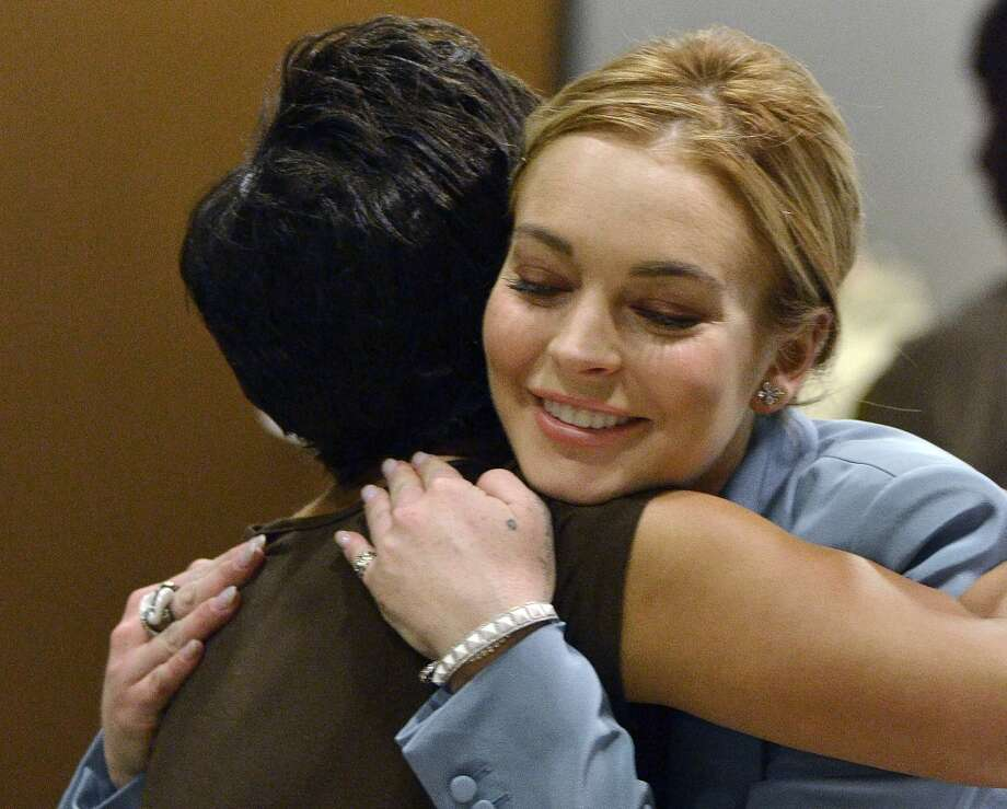 Lindsay Lohan, right, embraces her attorney, Shawn Chapman Holley after a progress report on her probation for theft charges at Los Angeles Superior Court Thursday, March 29, 2012. A judge ended Lindsay Lohan's supervised probation on Thursday, giving the actress her freedom after nearly two years of constant court hearings and threats of jail. Lohan thanked Superior Court Judge Stephanie Sautner for her patience and let out a sigh of relief as she exited the courtroom after the brief hearing.