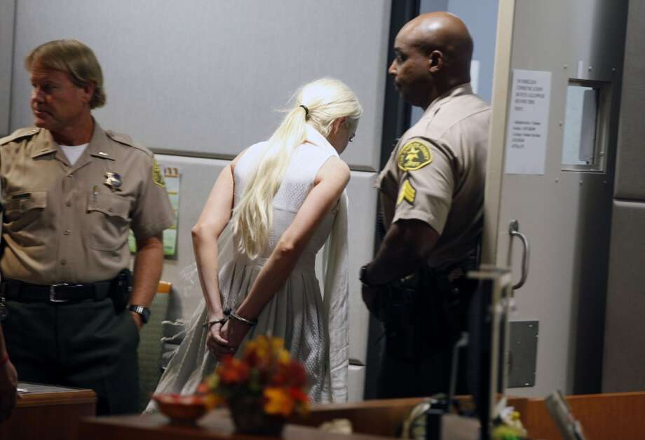 Lindsay Lohan is led away in handcuffs at her probation progress report hearing at the Airport Courthouse on October 19, 2011 in Los Angeles, California.  Judge Stephanie Sautner suspended Lohan's probation after Lohan was terminated by the Downtown Women's Center for repeatedly failing to appear for community service.