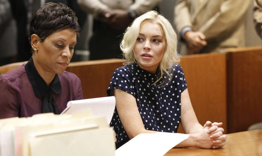 Actress Lindsay Lohan sits with her lawyer inside the Los Angeles Superior Court in Los Angeles on Nov. 2, 2011. Troubled US actress Lohan was sentenced to 30 days behind bars after admitting she had violated the terms of her probation after previous legal tangles.