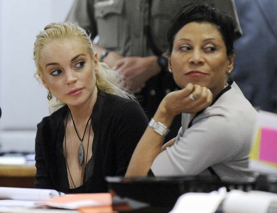 Lindsay Lohan, left, appears in Los Angeles Superior Court with her attorney Shawn Chapman Holley, where a judge is to decide whether an allegation that the actress stole a $2,500 necklace can be resolved without going to trial, Wednesday, Feb. 23, 2011.