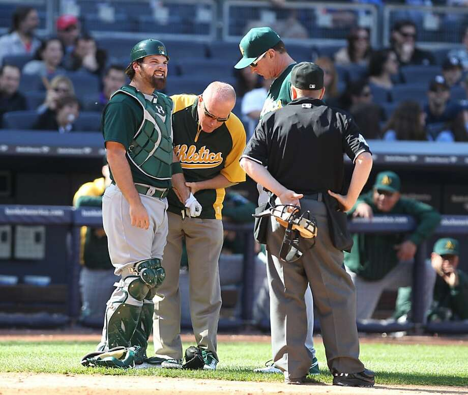 Oakland Athletics catcher Derek Norris has his hand examined as manager manager Bob Melvin and umpire Jerry Meals watch in the ninth inning of a baseball game against the New York Yankees in New York on Sunday, May 5, 2013. (AP Photo/Peter Morgan) Photo: Peter Morgan, Associated Press