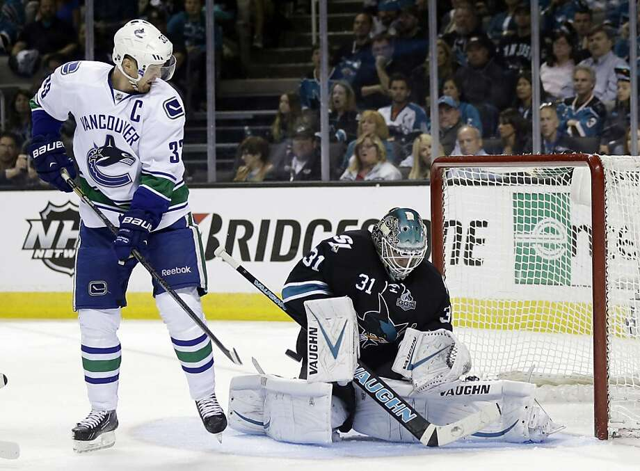 San Jose Sharks goalie Antti Niemi, right, of Finland, stops as shot next to Vancouver Canucks center Henrik Sedin, of Sweden, during the second period of Game 3 of their first-round NHL hockey Stanley Cup playoff series in San Jose, Calif., Sunday, May 5, 2013. (AP Photo/Marcio Jose Sanchez) Photo: Marcio Jose Sanchez, Associated Press