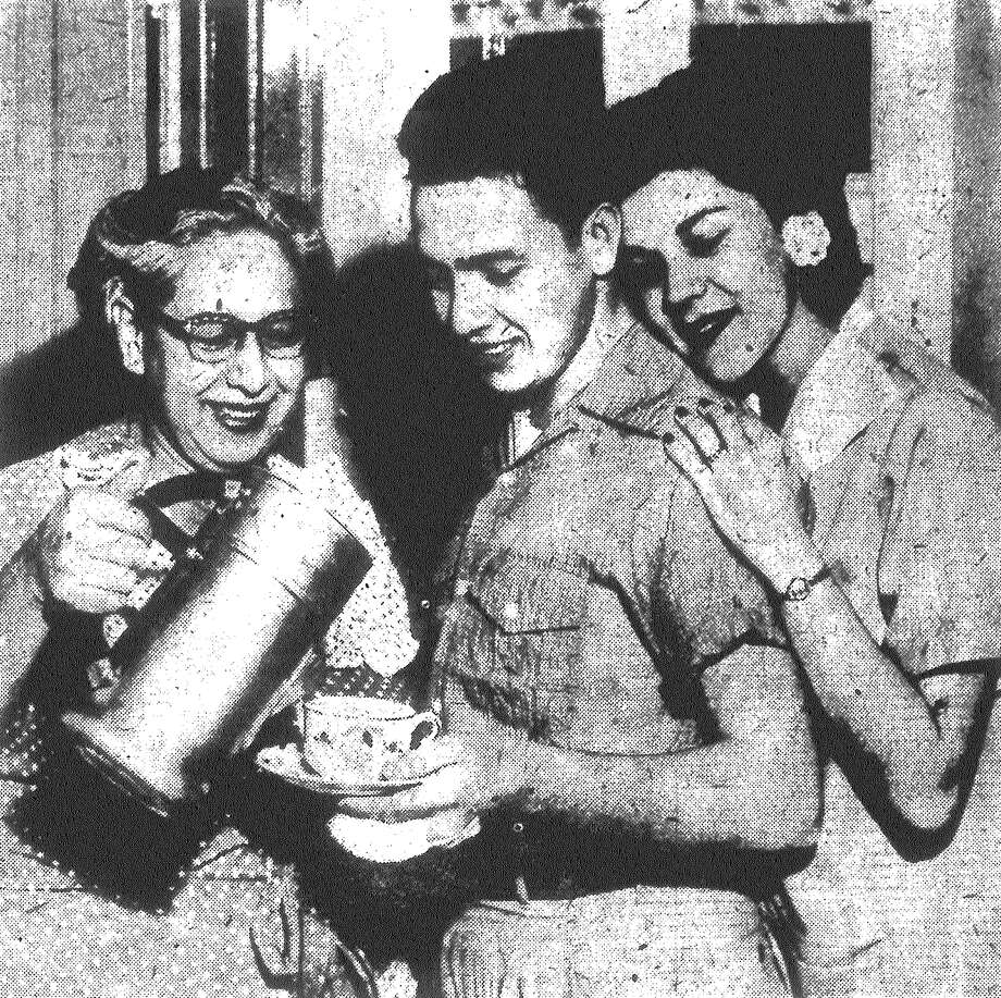 Mrs. Albert de la Garza serves son 1st Lt. Albert de la Garza and daughter-in-law Gloria a hot cup of coffee. De la Garza is San Antonio's second POW to return home. Published in the San Antonio Light May 4, 1953. Photo: File Photo