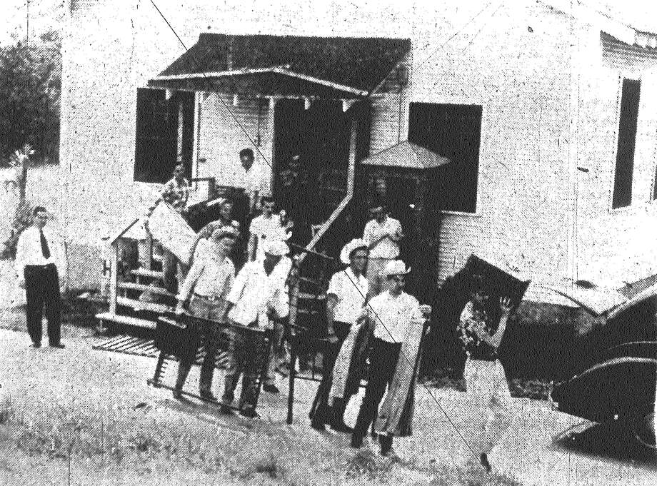 Moving day! When the word was given to move into the new dormitory, St. Mary's University students dismantled their own beds and picked up their books and clothes and moved in a body. This group is shown leaving an old frame building which housed approximately 30 of the resident students. Published in the San Antonio Express May 10, 1953. Photo: File Photo