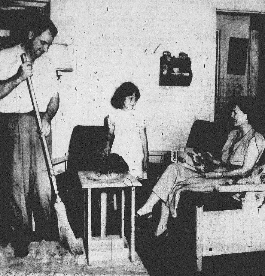 """Man may work from sun to sun, but a woman's work is never done,"" except on Mother's Day, when Mom gets to sit back and take it easy. Mrs. Carl McClure settles back with a magazine while husband and daughter, Belinda, 5, sweep and dust on ""Mom's Day."" Published in the San Antonio Express May 10, 1953. Photo: File Photo"