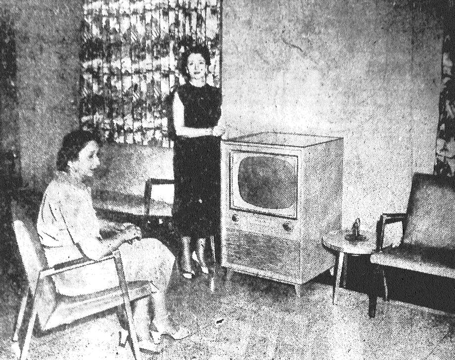 Mrs. C. Dalkawitz drops in a coin as Gladys Dalkawitz watches a coin-operated television set recently installed at the San Antonio Municipal Airport. According to Assistant Aviation Director J.R. Saunders, the spacious lounge featuring TV has become a big attraction at the terminal. The set plays for an hour on 25 cents. Published in the San Antonio Light May 28, 1953. Photo: File Photo