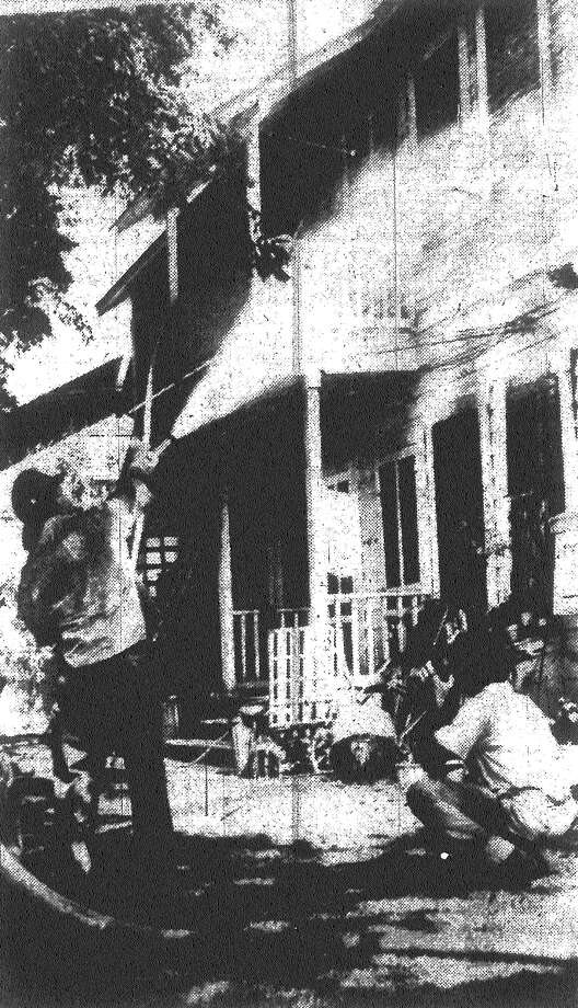 Talk about devotion to duty! San Antonio Express Photographer Johnny Tarsikes (right) crouches underneath a fire hose for pictures as firemen battle flames in the 200 block of Queen Anne Court. What's so devoted about that? It was Tarsikes' house that was on fire! Published in the San Antonio Express May 28, 1953. Photo: File Photo
