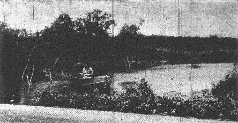 """This is not a secluded fishing hole, as first glance might indicate. The half-acre of water has accumulated on low, vacant property in the 3300 block of S. Gevers Street, causing Highland Park residents to dub it """"Lake Gevers."""" Complaints reaching the city health department call it a mosquito breeder. That's Mrs. Edna Chelkowski proving the water is deep enough for boating. And that's Gevers Street in the foreground. Nearby residents say city officials won't do anything about cleaning it up. Published in the San Antonio Express May 29, 1953. Photo: File Photo"""