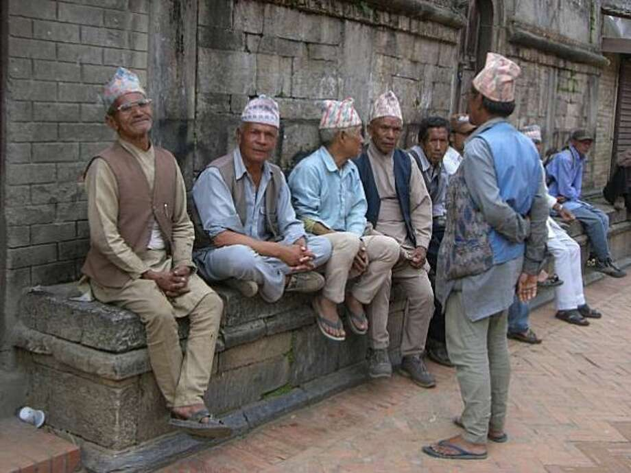 Newari gentlemen wearing topis – tradition caps --relax in downtown Kathmandu