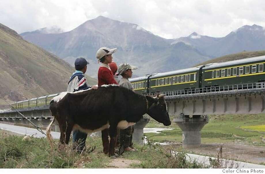 Tibetan children watch as the first train from Lhasa Railway Station travels on the Tibetan grasslands near Lhasa, Tibet,