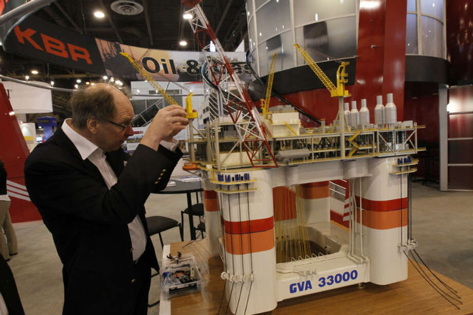 Peter Ankarsward prepares his model off-shore drilling rig at the Offshore Technology Conference. Photo: Cody Duty, Houston Chronicle