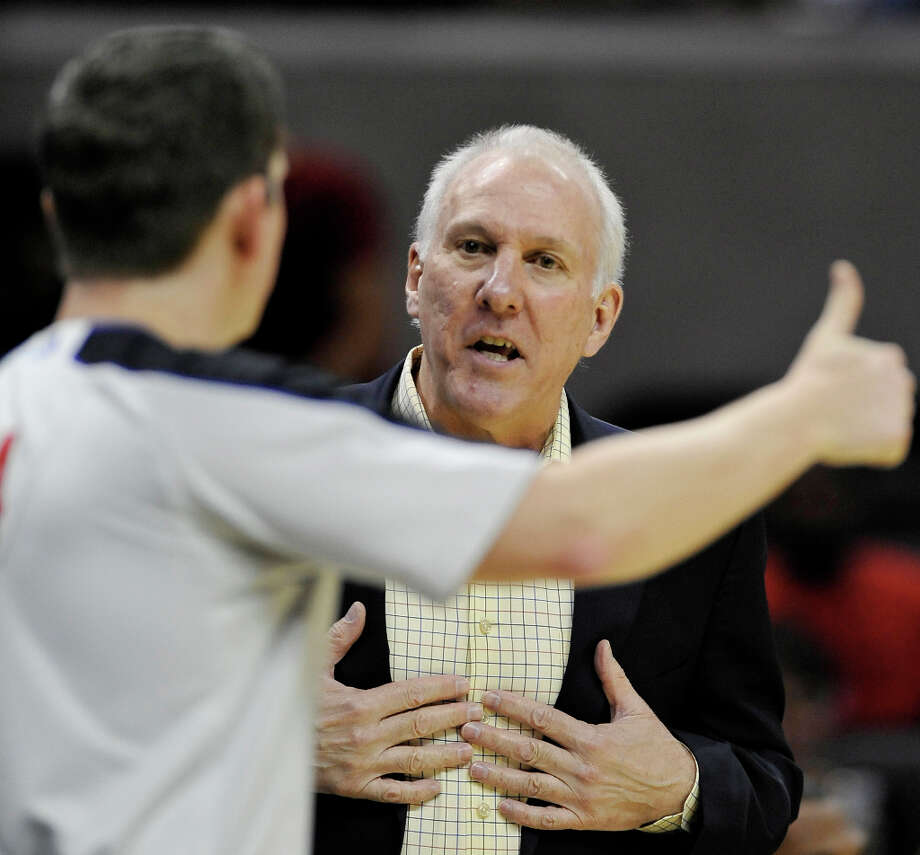 San Antonio Spurs head coach Gregg Popovich, right, talks with referee Nick Buchert during the first half of an NBA basketball game against the Atlanta Hawks, Wednesday, Oct. 10, 2012, in San Antonio. (AP Photo/Darren Abate) Photo: Darren Abate, Associated Press / FR115 AP
