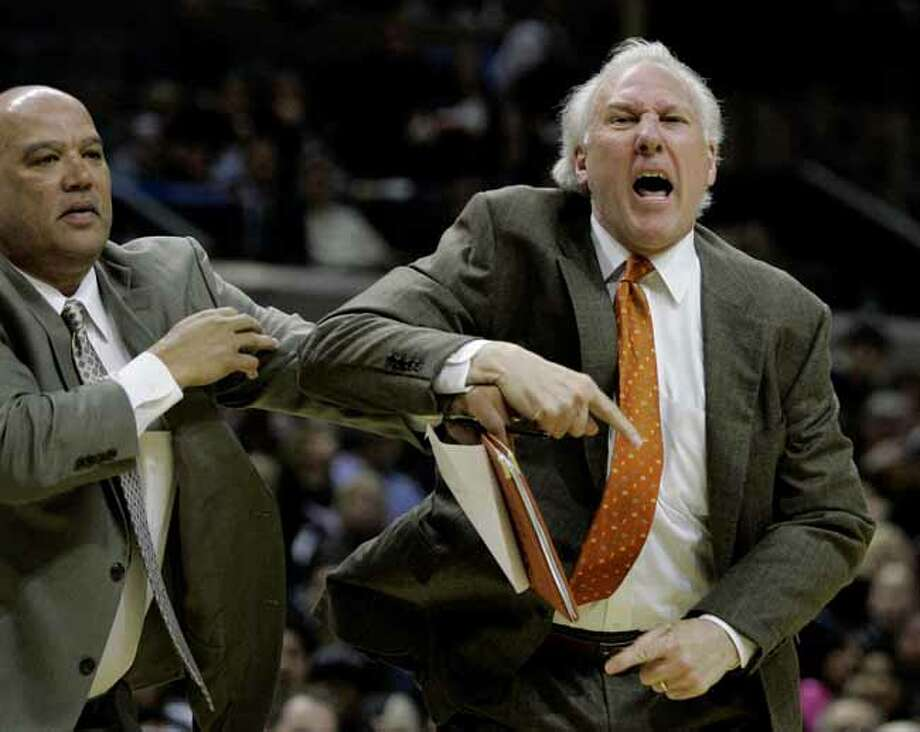San Antonio Spurs coach Gregg Popovich, right, is held back by assistant coach Don Newman, left, while arguing with officials during the second quarter of their NBA basketball game against the Indiana Pacers in San Antonio, Thursday, March 6, 2008. Popovich was ejected from the game. (AP Photo/Eric Gay) Photo: Eric Gay, Associated Press / AP