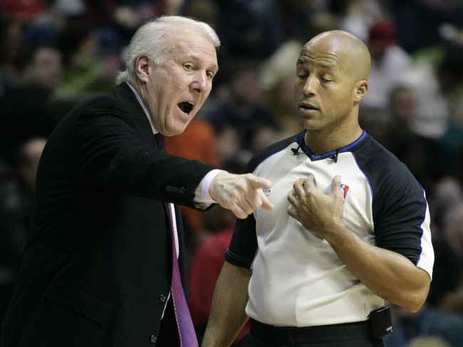 NBA official Marc Davis, right, listens to San Antonio Spurs coach Gregg Popovich make his point in the first half of an NBA basketball game against the Detroit Pistons, Sunday, Feb. 21, 2010, in Auburn Hills, Mich. (AP Photo/Duane Burleson) Photo: Duane Burleson, Associated Press / FR38952 AP