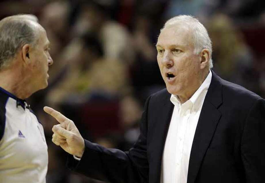 San Antonio Spurs coach Gregg Popovich, right, talks to official Kevin Fehr, left, during the second quarter of an NBA basketball game against the Houston Rockets, Thursday, Dec. 29, 2011, in Houston. (AP Photo/David J. Phillip) Photo: David J. Phillip, Associated Press / AP