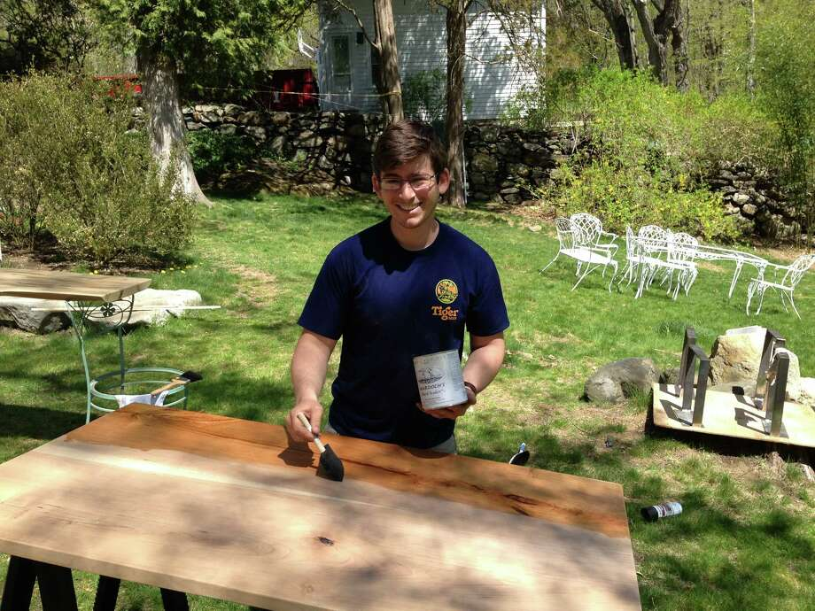 Eli Arnow, 24, of Pound Ridge, puts on the first coat of tung oil finish to a table he and partner Matt Rohrs created. Pound Ridge, N.Y., May 3, 2013. Photo: Tyler Woods
