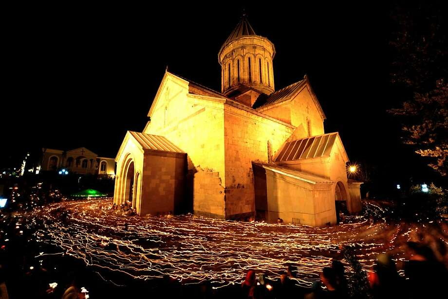 Candles carried by Orthodox believers leave light trails around the Sion Cathedral in Tbilisi in this long-