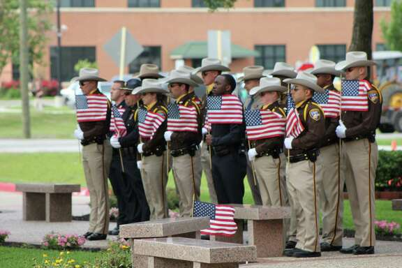 Officers from several Fort Bend County law enforcement agencies placed an American flag around the Peace Officers' Memorial during the ceremony.