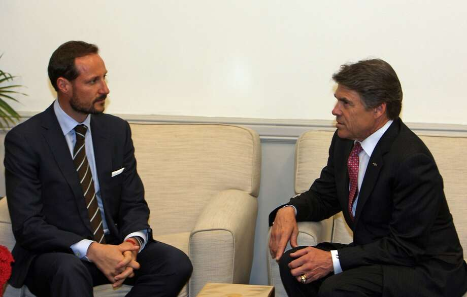 Gov. Rick Perry speaks to Norway's Crown Prince Haakon during OTC 2013 at Reliant Park Monday, May 6, 2013, in Houston. ( James Nielsen / Houston Chronicle )
