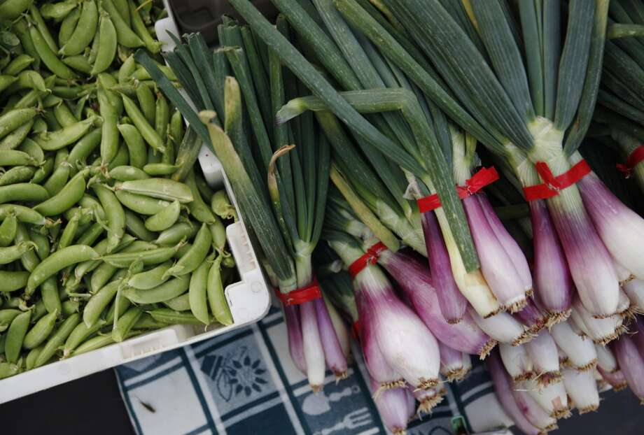 Snap peas and spring onions are seen at the Everything Under the Sun stand at the Ferry Plaza Farmers Market.