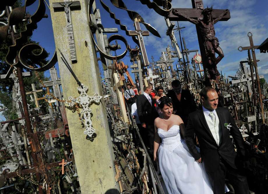 "This unidentified couple surely didn't have to worry about vampires showing up at the ""Hill of Crosses"" (Krizu Kalnas), in Lithuania, on September 3, 2011. Photo: JOE KLAMAR, AFP/Getty Images / 2011 AFP"